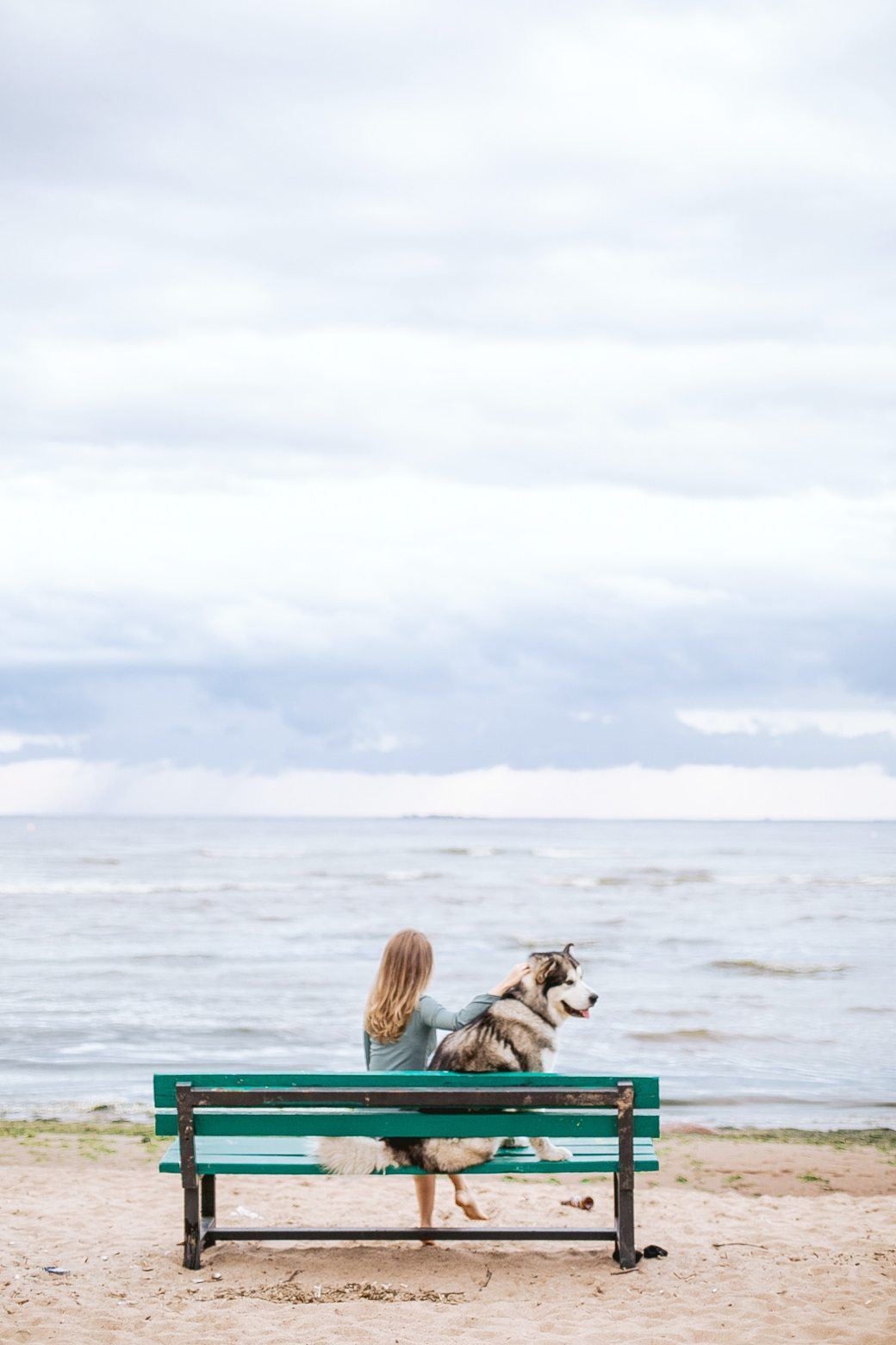 woman-sitting-in-a-beach-bench-with-her-pet-3663040 (1)
